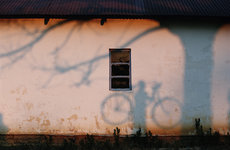 Fotó: Chris Johns: A shadow of a man holding a bicycle is cast on a wall near the Zambezi River, 1996 © National Geographic